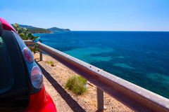 Red car parked near the view point on the sea in Cala Regina, Sa Stock Photography