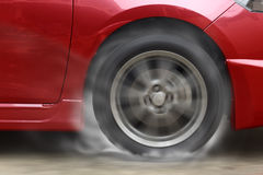Red car racing spinning wheel burns rubber on floor. Red car racing spinning wheel burns rubber on floor stock images