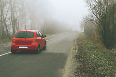 Red car rides along a rural road in a fog between trees Stock Photo