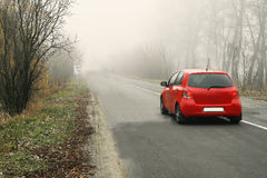 Red car rides along a rural road in a fog between trees Stock Image