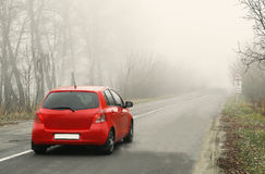Red car rides along a rural road in a fog between trees Royalty Free Stock Photography