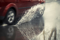 Red car rides on big puddle. Water splash. Stock Photography