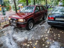 Free Red Car Rides In The Yard On A Wet Road In The Rain . Beautiful Splashes Of Water From Under The Wheels. Stock Photo - 126302050