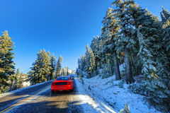 Red car on snowy and icy winter road Stock Photography