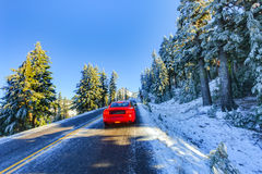 Red car on snowy and icy winter road Royalty Free Stock Photo