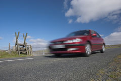 Red car speeding on mountain road in Devon Stock Photo