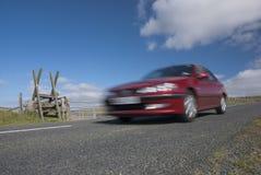Red car speeding on mountain road in Devon Stock Photo