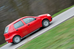 Red car speeding in panned motion Royalty Free Stock Photo