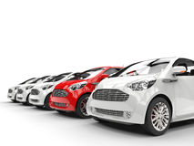 Red Car Stands Out in a Row of White Cars Royalty Free Stock Image