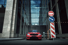 Red car stay on asphalt road in the city at daytime Stock Image