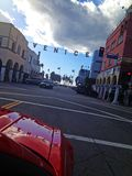 Red car on streets of Venice. Red car driving on road with sign for Venice against blue skies on sunny day stock photo