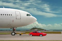 Red car is towing airplane. Leader. Concept. Red powerful sports car is towing the big airplane. Concept of leadership, power & help. Sky area is free for your stock images
