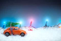 Red car toy carrying a Christmas tree with Christmas lights in t Royalty Free Stock Photos