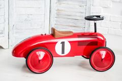 Red car toy in front of white wall. Red car toy with number one sign in front of white wall Royalty Free Stock Photo