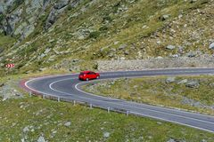Red car on Transfagarasn winding mountain road with at high altitude in Carpathian Mountains Stock Photos