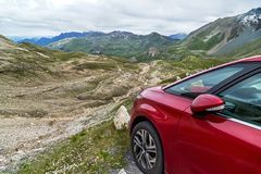 Red car for traveling is standing on the mountain road in the Alps, Austria. Stock Photos
