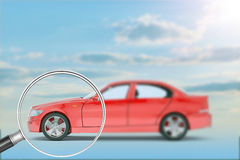 Red car under loupe. On nature blue sky background Royalty Free Stock Image