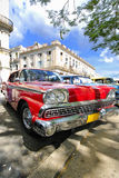 Red car under tree branches in havana, cuba