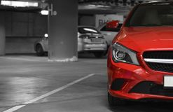 Red car on the underground parking. Side of red car on the underground parking Stock Image
