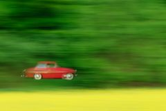 Red car veteran on the road between the trees. Beautiful car veteran passes between green trees. In the foreground there is a field with yellow rapeseed oil. It Royalty Free Stock Photos