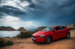 Red car Volvo v40 standing on the edge of a cliff against the stormy sky. Royalty Free Stock Image