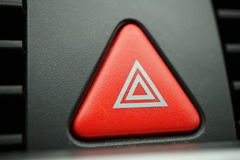 Red car Warning button with a white triangle switching all the vehicle outdoor indicators as a symbol of  caution, warning and po Royalty Free Stock Photography