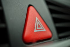 Red car Warning button with a white triangle switching all the vehicle outdoor indicators as a symbol of  caution, warning and po Royalty Free Stock Images