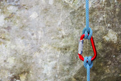 Red carabiner with climbing rope on rocky background Stock Photos