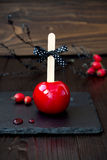 Red caramel apple. Close up. Traditional dessert recipe for Halloween party. Selective focus Royalty Free Stock Images