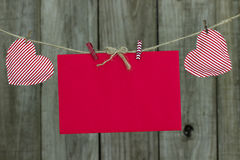 Red card envelope and red and white striped hearts hanging on clothesline by wood fence Royalty Free Stock Photos