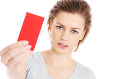 Red card. A picture of a serious woman showing a red card over white background Royalty Free Stock Photo