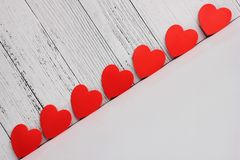 Red cardboard hearts are arranged in a row. Design and decoration for Valentine`s Day. concept of love. Copy Space stock photography