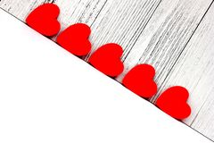 Red cardboard hearts are arranged in a row. Design and decoration for Valentine`s Day. concept of love. Copy Space royalty free stock photography
