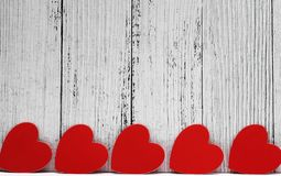 Red cardboard hearts are arranged in a row. Design and decoration for Valentine`s Day. concept of love. Copy Space royalty free stock photo