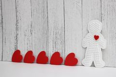 Red cardboard hearts are arranged in a row on a white wooden background. Plastic figure of a man with a red heart. concept of love. Valentine`s day. Copy Space royalty free stock photography