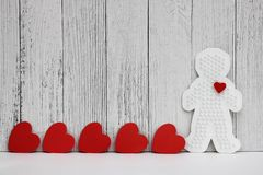 Red cardboard hearts are arranged in a row on a white wooden background. Plastic figure of a man with a red heart. concept of love. Valentine`s day. Copy Space stock image