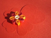 Red cardboard hearts design. Red cardboard hearts arranged as four leaves clover shape, with quilling flower in center stock photos