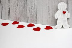 Red cardboard hearts are on a white background. Plastic figure of a man with a red heart. concept of love. Valentine`s day. Copy Space stock image