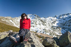 Red cardigan woman sitting posing on peak mountains Royalty Free Stock Image