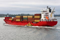 Red cargo container ship at sea. Bright red cargo container ship sailing at sea, with harbour master pilot boat alongside Royalty Free Stock Photography