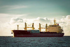 Red cargo ship. Bulk carrier moving entering the port of Riga royalty free stock photography
