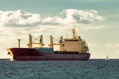 Red cargo ship. Bulk carrier moving entering the port of Riga royalty free stock image