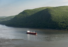 Red Cargo Ship on the Hudson River. Red cargo ship slowly moving north up the Hudson River with the Hudson Highlands in the background near Cold Spring, New York Stock Image