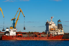 Red cargo ship. Loading in the port of Riga, Europe stock photography