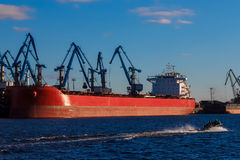 Red cargo ship. Loading in the port of Riga, Europe Royalty Free Stock Photo
