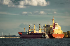 Red cargo ship and the tug ship. Towing it to the port Royalty Free Stock Images