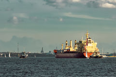 Red cargo ship and the tug ship. Towing it to the port stock image