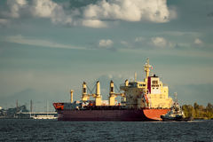 Red cargo ship and the tug ship. Towing it to the port Stock Photos