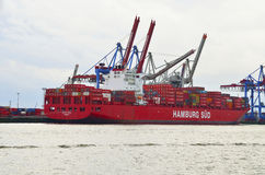 Red cargo ship unloaded by cranes in Hamburg port, Germany Stock Photography