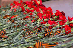 Red carnations and ribbon on a memorial Stock Image